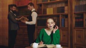 Γυναίκα διαβασμένο στο βιβλιοθήκη καφέ βιβλίων και κατανάλωσης από το φλυτζάνι Καφές λογοτεχνίας με το χαριτωμένα κορίτσι και τα  απόθεμα βίντεο