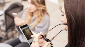 Γυναίκα δύο στον καφέ που χρησιμοποιεί app το smartphone που παίζει το κοινωνικό δίκτυο Στοκ Εικόνες
