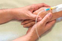 Γυναίκα εκμετάλλευσης ανδρών, ασθενής, χέρι με έναν σωλήνα της έγχυσης ιατρικής σε ένα κρεβάτι Στοκ φωτογραφία με δικαίωμα ελεύθερης χρήσης