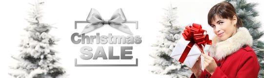 Γυναίκα εμβλημάτων πώλησης Χριστουγέννων με το κιβώτιο δώρων στα άσπρα WI υποβάθρου Στοκ Φωτογραφία