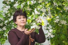 Γυναίκα ενάντια στο ανθίζοντας Apple-δέντρο Στοκ Φωτογραφία