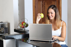 Γυναίκα επιχειρηματίας που κοιτάζει βιαστικά ένα lap-top και που τρώει στο σπίτι στοκ εικόνα