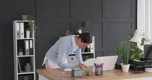 Γυναίκα επιχειρηματιών που γράφει στη συγκολλητική σημείωση στο γραφείο απόθεμα βίντεο