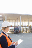 Γυναίκα εργαζόμενος που γράφει στην περιοχή αποκομμάτων εξετάζοντας τα φορτηγά που εισάγονται στη ναυτιλία του ναυπηγείου Στοκ Εικόνες