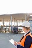 Γυναίκα εργαζόμενος που γράφει στην περιοχή αποκομμάτων εξετάζοντας τα φορτηγά που εισάγονται στη ναυτιλία του ναυπηγείου Στοκ φωτογραφίες με δικαίωμα ελεύθερης χρήσης