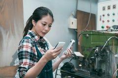 Γυναίκα εργαζόμενος που ελέγχει την άλεση που επεξεργάζεται το προϊόν στη μηχανή Στοκ φωτογραφίες με δικαίωμα ελεύθερης χρήσης