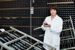 Γυναίκα εργαζόμενος που ελέγχει τη δευτεροβάθμια ζύμωση στοκ εικόνες