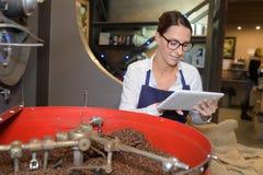 Γυναίκα εργαζόμενος στον καφέ στο εργοστάσιο καφέ Στοκ Εικόνες