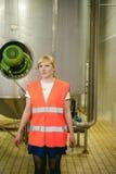 Γυναίκα εργαζόμενος στο εργοστάσιο μπύρας γυναίκα πορτρέτου στην τήβεννο, που στέκεται στη παραγωγή προϊόντων γραμμών υποβάθρου,  Στοκ εικόνα με δικαίωμα ελεύθερης χρήσης