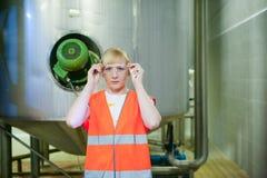 Γυναίκα εργαζόμενος στο εργοστάσιο μπύρας γυναίκα πορτρέτου στην τήβεννο, που στέκεται στη παραγωγή προϊόντων γραμμών υποβάθρου,  Στοκ εικόνες με δικαίωμα ελεύθερης χρήσης