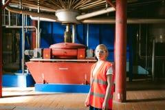 Γυναίκα εργαζόμενος στο εργοστάσιο μπύρας γυναίκα πορτρέτου στην τήβεννο, που στέκεται στη παραγωγή προϊόντων γραμμών υποβάθρου,  Στοκ Εικόνες