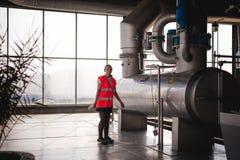 Γυναίκα εργαζόμενος στο εργοστάσιο μπύρας γυναίκα πορτρέτου στην τήβεννο, που στέκεται στη παραγωγή προϊόντων γραμμών υποβάθρου,  Στοκ Εικόνα