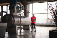 Γυναίκα εργαζόμενος στο εργοστάσιο μπύρας γυναίκα πορτρέτου στην τήβεννο, που στέκεται στη παραγωγή προϊόντων γραμμών υποβάθρου,  Στοκ φωτογραφίες με δικαίωμα ελεύθερης χρήσης