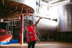 Γυναίκα εργαζόμενος στο εργοστάσιο μπύρας γυναίκα πορτρέτου στην τήβεννο, που στέκεται στη παραγωγή προϊόντων γραμμών υποβάθρου,  Στοκ Φωτογραφίες