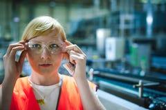 Γυναίκα εργαζόμενος στο εργοστάσιο μπύρας γυναίκα πορτρέτου στην τήβεννο, που στέκεται στη παραγωγή προϊόντων γραμμών υποβάθρου,  Στοκ φωτογραφία με δικαίωμα ελεύθερης χρήσης