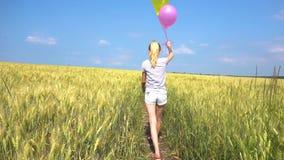 Γυναίκα εφήβων με τα μπαλόνια που περπατά στον τομέα σε σε αργή κίνηση απόθεμα βίντεο