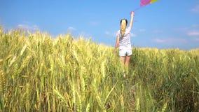 Γυναίκα εφήβων με τα μπαλόνια που περπατά στον τομέα απόθεμα βίντεο