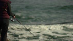 Γυναίκα θαλάσσιου ψαρέματος με μια ράβδο αλιείας απόθεμα βίντεο