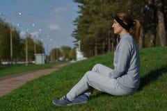Γυναίκα ικανότητας με τη μουσική συνεδρίασης και ακούσματος smartphone στο πάρκο πόλεων Στοκ φωτογραφία με δικαίωμα ελεύθερης χρήσης