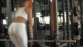 Γυναίκα ικανότητας που ανυψώνει barbell για το μυ γλουτών κατάρτισης στην αθλητική λέσχη φιλμ μικρού μήκους