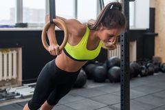 Γυναίκα ικανότητας που κάνει τα όπλα κατάρτισης ώθησης UPS με τα δαχτυλίδια γυμναστικής στο γυμναστικής αθλητισμό τρόπου ζωής ένν Στοκ φωτογραφία με δικαίωμα ελεύθερης χρήσης