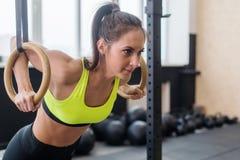 Γυναίκα ικανότητας που κάνει τα όπλα κατάρτισης ώθησης UPS με τα δαχτυλίδια γυμναστικής στο γυμναστικής αθλητισμό τρόπου ζωής ένν Στοκ εικόνα με δικαίωμα ελεύθερης χρήσης