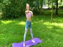 Γυναίκα ικανότητας που κάνει την άσκηση στον πράσινο χορτοτάπητα απόθεμα βίντεο