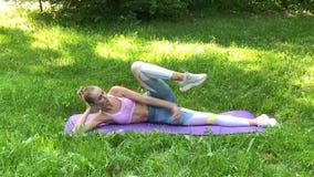 Γυναίκα ικανότητας που κάνει την άσκηση στον πράσινο χορτοτάπητα φιλμ μικρού μήκους