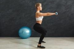 Γυναίκα ικανότητας που κάνει τη στάση οκλαδόν στο γκρίζο υπόβαθρο Στοκ φωτογραφία με δικαίωμα ελεύθερης χρήσης