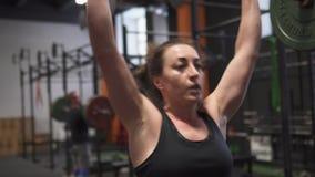 Γυναίκα ικανότητας που κάνει barbell την άσκηση προωθητών στη γυμναστική απόθεμα βίντεο