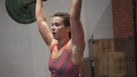 Γυναίκα ικανότητας που κάνει barbell τη διαγώνια κατάρτιση προωθητών στη γυμναστική απόθεμα βίντεο