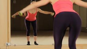 Γυναίκα ικανότητας που συμμετέχεται στη γυμναστική με τον αλτήρα ενάντια στον καθρέφτη Τέλεια κινηματογράφηση σε πρώτο πλάνο άκρη απόθεμα βίντεο