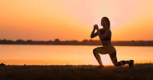 Γυναίκα ικανότητας που τεντώνει κάνοντας lunge την άσκηση τεντωμάτων Θηλυκά lunges κατάρτισης αθλητών τεντώματα έξω σε όμορφο απόθεμα βίντεο