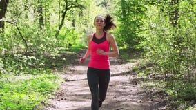 Γυναίκα ικανότητας που τρέχει την άνοιξη το ηλιόλουστο δάσος απόθεμα βίντεο