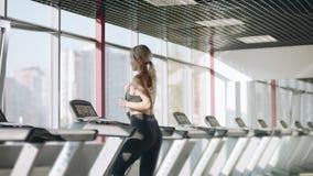 Γυναίκα ικανότητας που τρέχει treadmill στη γυμναστική Όμορφο κορίτσι που έχει την καρδιο κατάρτιση φιλμ μικρού μήκους