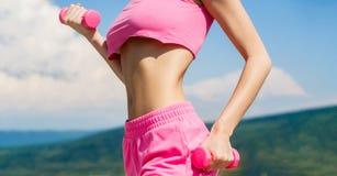 Γυναίκα ικανότητας στην κατάρτιση Η φίλαθλη γυναίκα κάνει τις ασκήσεις με τους αλτήρες Προκλητικό κορίτσι αθλητικής ικανότητας, α στοκ εικόνες