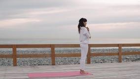 Γυναίκα ικανότητας στην πρακτική γιόγκας στην παραλία απόθεμα βίντεο