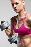 Γυναίκα ικανότητας bodybuilder με τους αλτήρες ξανθό κορίτσι ομορφιάς με τους μυς Στοκ Φωτογραφίες