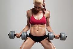 Γυναίκα ικανότητας bodybuilder με τους αλτήρες όμορφο ξανθό κορίτσι με τους μυς Στοκ Εικόνες
