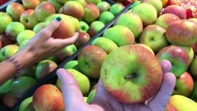 Γυναίκα και άνδρας που επιλέγουν τα φρέσκα οργανικά μήλα στην υπεραγορά Λεωφόρος αγορών στην Ασία αγορές τροφίμων απόθεμα βίντεο