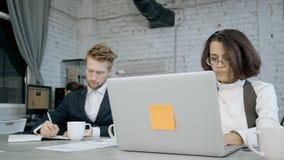 Γυναίκα και άνδρας που χρησιμοποιούν το lap-top, την ημερήσια διάταξη και την εργασία στην αρχή φιλμ μικρού μήκους