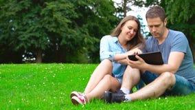 Γυναίκα και άνδρας που χρησιμοποιούν υπολογιστή tablet στο πάρκο απόθεμα βίντεο