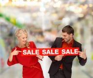 Γυναίκα και άνδρας που δείχνουν το δάχτυλο το κόκκινο σημάδι πώλησης Στοκ εικόνα με δικαίωμα ελεύθερης χρήσης