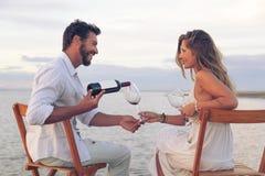 Γυναίκα και άνδρας που πίνουν το κόκκινο κρασί στην παραλία Στοκ εικόνα με δικαίωμα ελεύθερης χρήσης