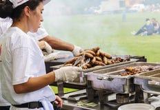 Γυναίκα και άνδρας που χειρίζονται τα μεγάλα λουκάνικα και το κρέας Στοκ Εικόνες