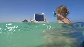 Γυναίκα και άνδρας στη θάλασσα που κάνει τις φωτογραφίες διακοπών απόθεμα βίντεο