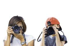 Γυναίκα και αγόρι χεριών που κρατούν τη κάμερα που παίρνει τις εικόνες σε ένα άσπρο υπόβαθρο στοκ εικόνα με δικαίωμα ελεύθερης χρήσης