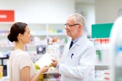 Γυναίκα και αποθηκάριος με τη συνταγή στο φαρμακείο στοκ εικόνα με δικαίωμα ελεύθερης χρήσης