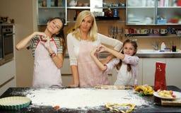 Γυναίκα και δύο κορίτσια στον πίνακα με τη ζύμη και τα μαγειρεύοντας εξαρτήματα Στοκ Εικόνες