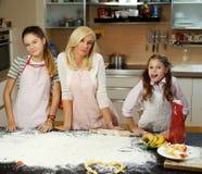 Γυναίκα και δύο κορίτσια στον πίνακα με τη ζύμη και τα μαγειρεύοντας εξαρτήματα Στοκ Φωτογραφίες